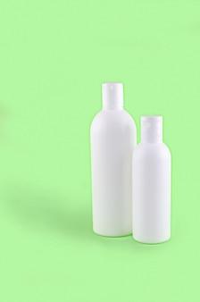 Dos botellas de cosméticos sobre fondo verde