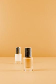 Dos botellas de esmalte de uñas en el fondo marrón abstracto