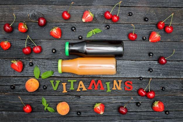 Dos botellas de jugo, la inscripción de color vitaminas y frutas. fondo de madera
