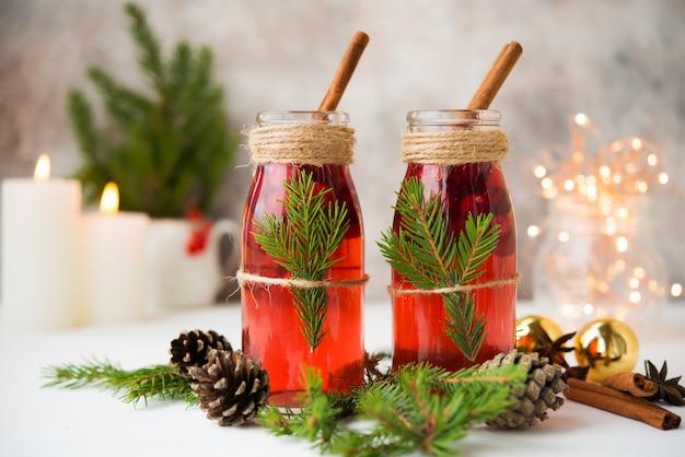 Dos botellas de vino caliente festivo tradicional con bayas y especias en una mesa blanca con guirnaldas navideñas y decoraciones navideñas