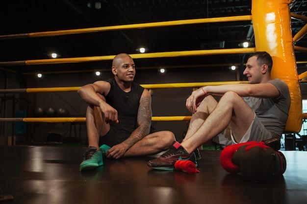 Dos boxeadores masculinos trabajando juntos en el gimnasio de boxeo