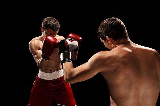 Dos boxeadores profesionales de boxeo en pared negra