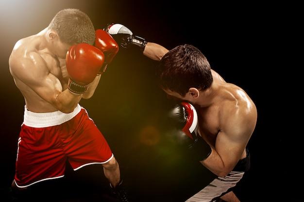 Dos boxeadores profesionales en la pared negra,