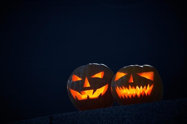 Dos brillantes calabazas de halloween en un oscuro