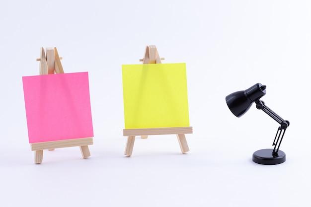 Dos caballetes de madera en miniatura con lienzo cuadrado de color en blanco o papel de nota