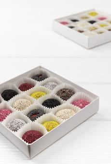 Dos cajas de bolas de energía de dulces veganos sobre mesa de madera blanca.