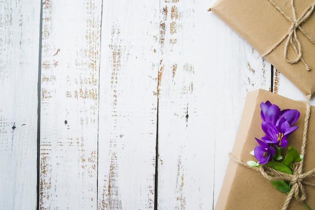 Dos cajas de cartón atadas con una cuerda en una vieja mesa de madera blanca