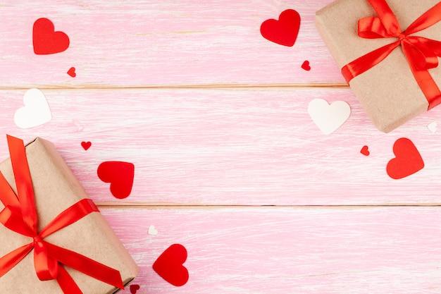 Dos cajas de regalo con lazo de cinta roja y corazones de confeti