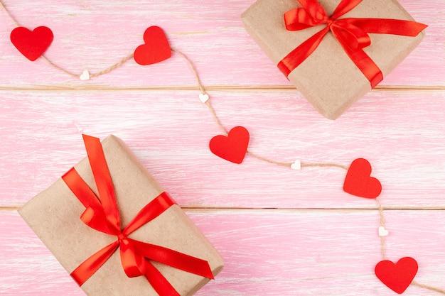 Dos cajas de regalo con lazo de cinta roja y corazones de papel