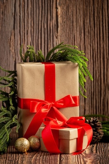 Dos cajas de regalo con lazo de cinta roja sobre fondo de madera