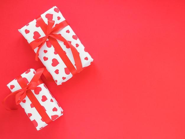 Dos cajas de regalo en mesa roja