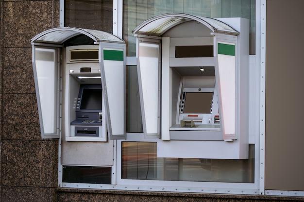Dos cajeros automáticos en la calle con operaciones actuales. pantalla en blanco para el diseño