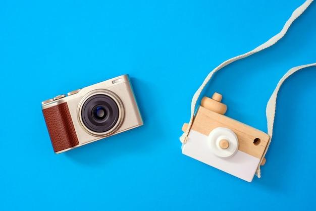 Dos cámaras, una moderna y otra antigua, comparadas una al lado de la otra, para academias de fotografía, aisladas en el fondo.
