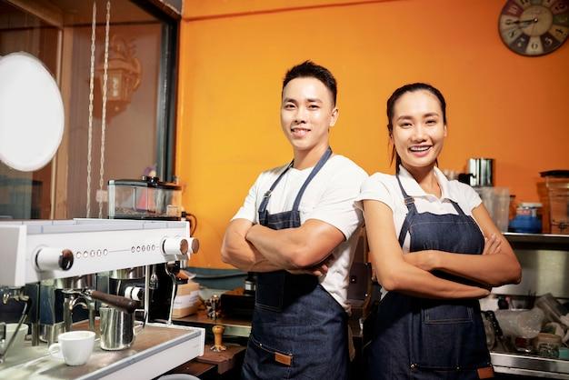 Dos camareros de pie en la cafetería.