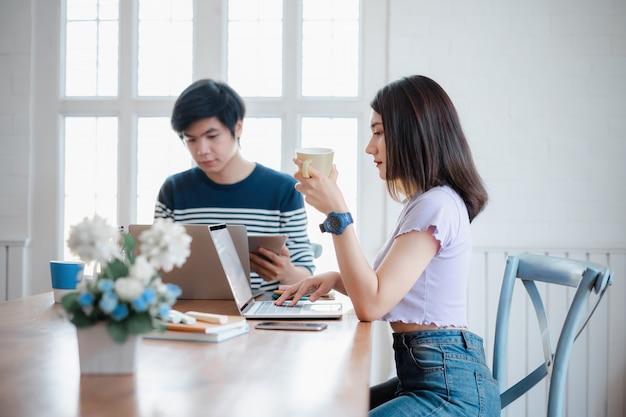 Dos cansados cansados jóvenes asiáticos trabajando en equipo trabajando en la computadora durante el día de trabajo en la oficina en casa