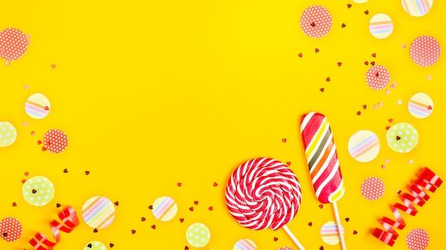 Dos caramelos multicolores entre círculos de papel de confeti, brillo y cintas festivas