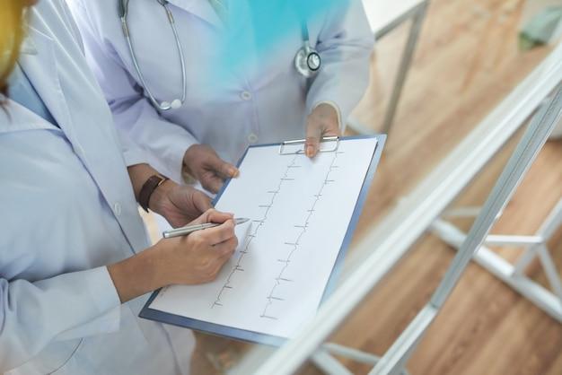 Dos cardiólogos recortados que revisan cardiogramas en el consultorio médico