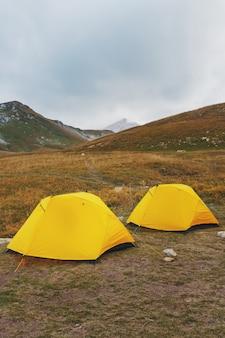 Dos carpas amarillas en un valle con montañas en otoño