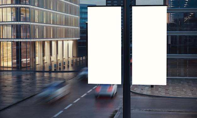 Dos carteles en blanco en la publicación en la noche de la ciudad