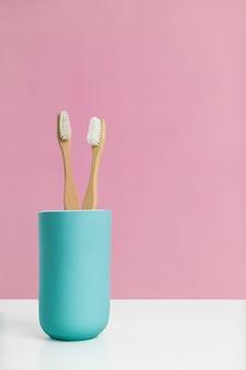 Dos cepillos de dientes ecológicos en un jarrón azul.