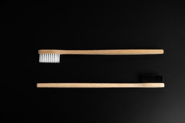 Dos cepillos de dientes de madera de bambú antibacterianos ecológicos con cerdas blancas y negras sobre una superficie negra