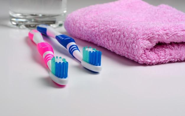 Dos cepillos de dientes rosas y toalla rosa.