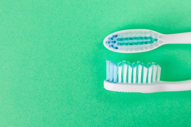 Dos cepillos de dientes sobre un fondo verde