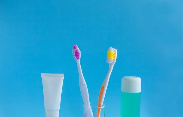 Dos cepillos de dientes en un vaso cerca de la pasta de dientes y enjuague contra un azul