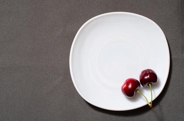 Dos cerezas en el borde de un plato vacío en la textura gris, copyspace, vista superior