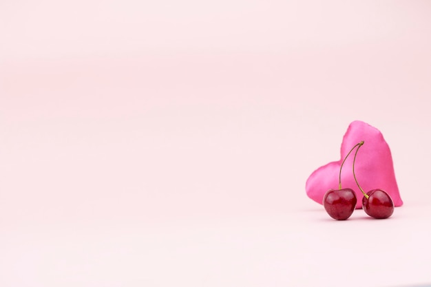 Dos cerezas maduras y un corazón de seda rosa sobre un fondo delicado