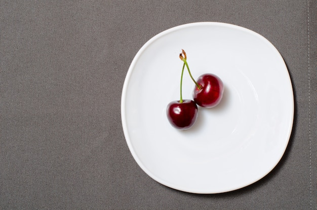 Dos cerezas en un plato blanco sobre la textura gris, espacio vacío