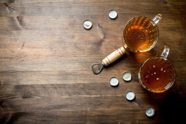Dos cervezas y abridor con tapas. en mesa de madera