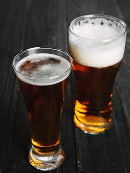 Dos cervezas en una mesa de madera oscura