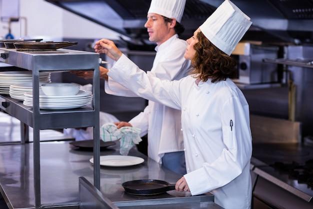 Dos chefs trabajando en la estación de pedidos en una cocina