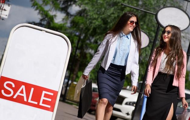 Dos chica asiática caminando con bolsas de compras