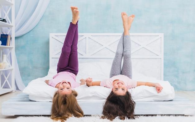 Dos chicas acostadas en la cama con las piernas cruzadas hacia arriba en casa