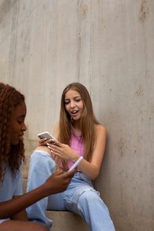 Dos chicas adolescentes pasar tiempo juntos en el parque de la pista de patinaje