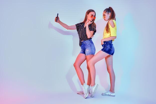 Dos chicas adolescentes en ropa de verano de pie en el estudio y haciendo selfie sobre fondo blanco.