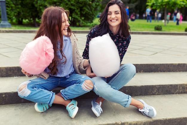 Dos chicas alegres divirtiéndose con algodón de azúcar al aire libre