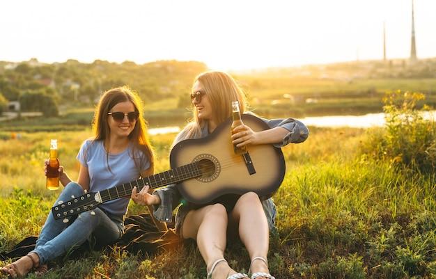 Dos chicas alegres y jóvenes amigos con gafas de sol, bebiendo cerveza y disfrutando del tiempo que pasaron juntos al atardecer.