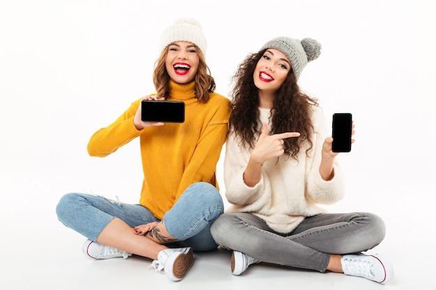 Dos chicas alegres con suéteres y sombreros sentados juntos en el suelo mientras muestran pantallas en blanco de teléfonos inteligentes sobre una pared blanca