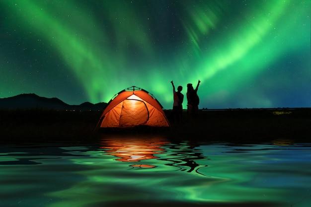 Dos chicas asiáticas acampando al aire libre en vacaciones con majestuosas luces del norte