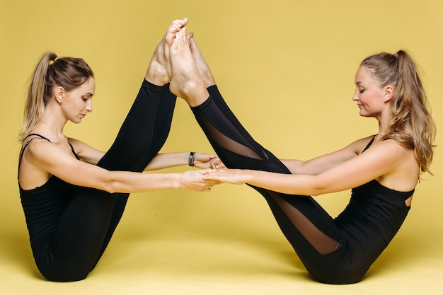 Dos chicas de atletismo en ropa deportiva negra haciendo ejercicio de yoga.
