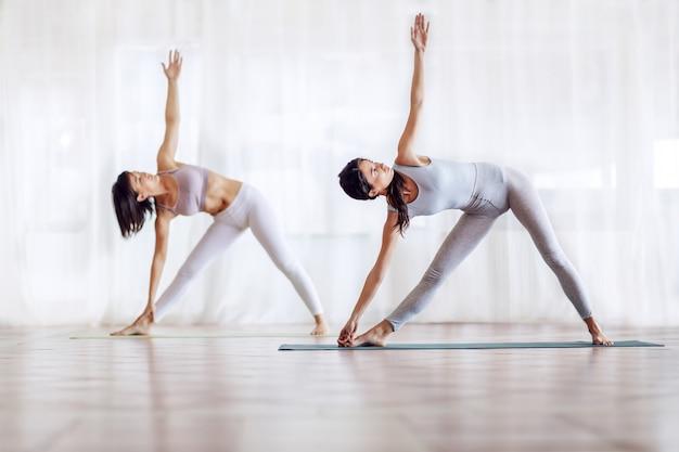 Dos chicas atractivas en forma en triángulo girado pose de yoga de pie sobre la estera en el estudio de yoga. enfoque selectivo en la chica con el pelo largo en primer plano.