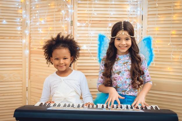 Dos chicas en atuendo festivo tocan el piano.