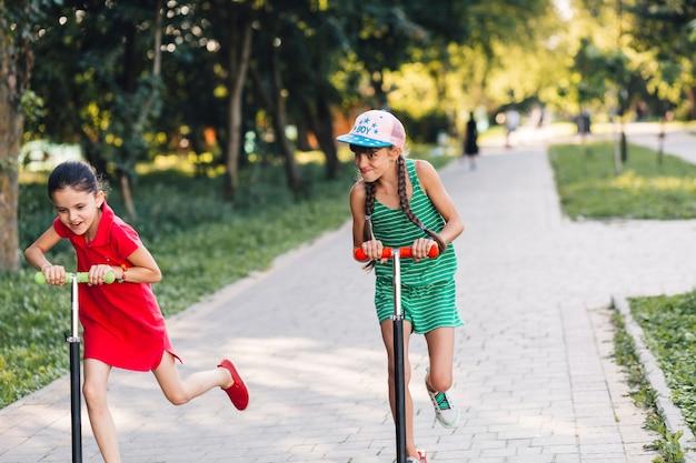 Dos chicas se burlan mientras viajan en patinete en el parque