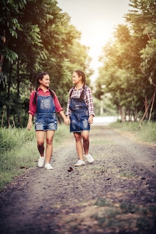 Dos chicas caminando por un camino forestal