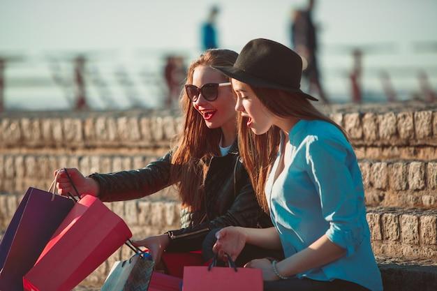 Dos chicas caminando con compras en calles de la ciudad
