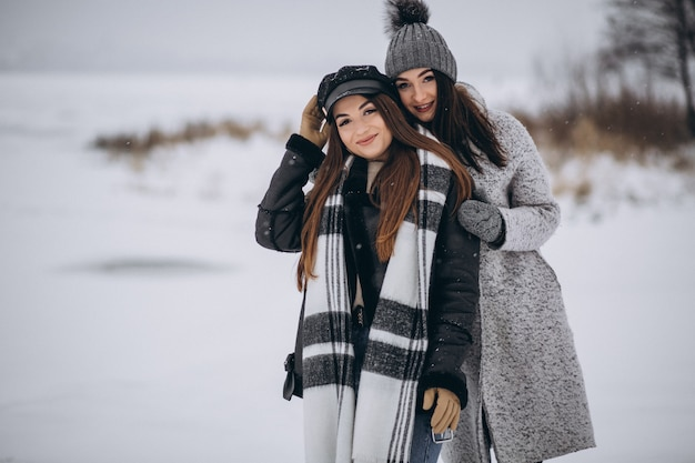 Dos chicas caminando juntas en un parque de invierno