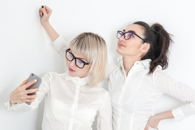 Dos chicas con camisas blancas y gafas hacen selfie en el teléfono